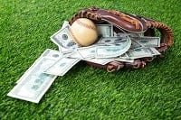 A glove, a baseball and dollar bills